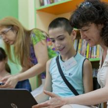Two librarians showing a girl and a boy how to use laptop computers.