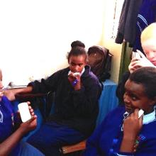 Visually impaired schoolchildren using audio devices.