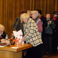 Senior citizens queue up to have their books signed by the famous author.