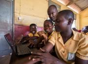 School children using a laptop.