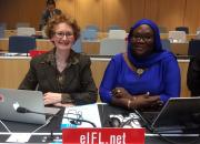 Teresa Hackett sitting next to Awe Cisse in the WIPO meeting hall.
