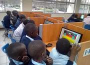 Children crowding around computers in the library.