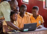 teacher showing children a laptop computer