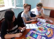 children playing a board game called cash flow at a table in the library