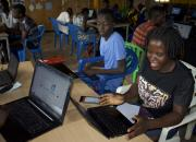 Women and young people learning how to use ICT, with laptops.