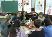 Girls sitting around a table making robots from Lego parts.