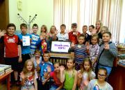 Children at Pelči Library (Latvia) celebrate the arrival of new equipment bought with the EIFL prize money - a touch screen computer monitor and a tablet e-book reader.