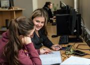 Two young girl students working at their desks in a university library.