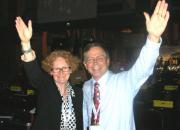 Happy photo of EIFL's Teresa Hackett and Bookshare's Jim Fruchtermann mark adoption of the treaty in Marrakesh, each with an arm raised in celebration.