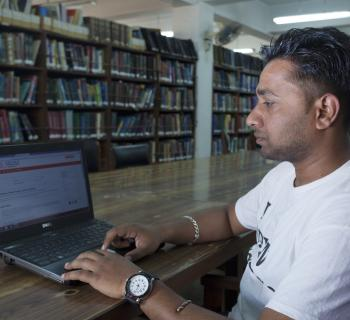 Researcher at a computer, in the library.
