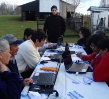 Farmers around a table, learning computer skills.
