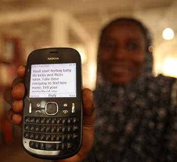A pregnant woman at Northern Regional Library in Ghana shows her mobile phones, where she receives health information.