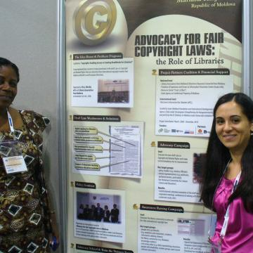Photo of EIFL copyright librarians from Ghana and Moldova at a poster session at IFLA. The poster is entitled 'Advocacy for access to knowledge, the role of libaries'.