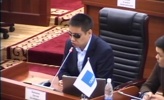 MP Dastan Bekeshev at a desk, addressing the meeting, through a microphone