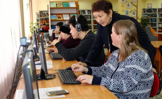 A librarian trains people with disability to use computers in the library.