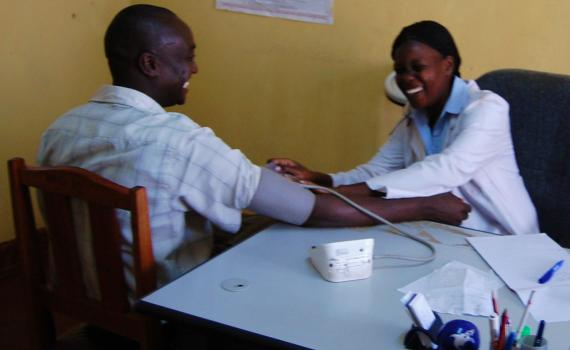 A health worker treating a patient at a clinic.