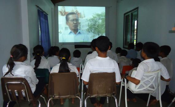 School children in Lveate Village watch filmed interviews with older villagers about their experience under the brutal Pol Pot regime.