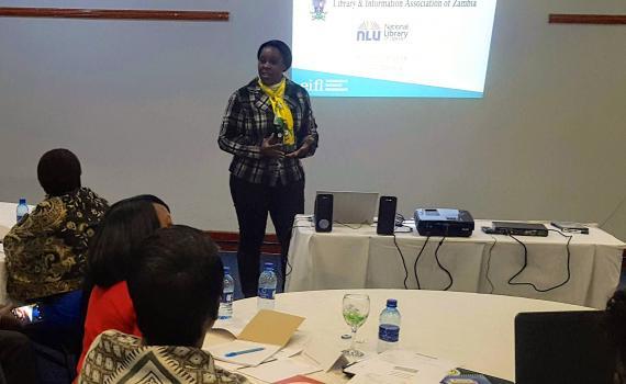 Velenasi Mwale Munsanje wecoming trainers, using a PowerPoint presentation.
